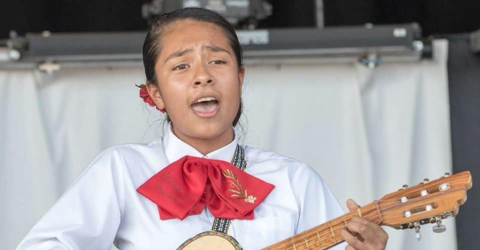 a young girl singing mariachi with a guitar